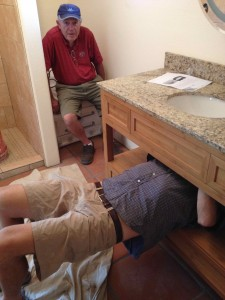 John watching from the composting toilet as Burt attaches the sink.