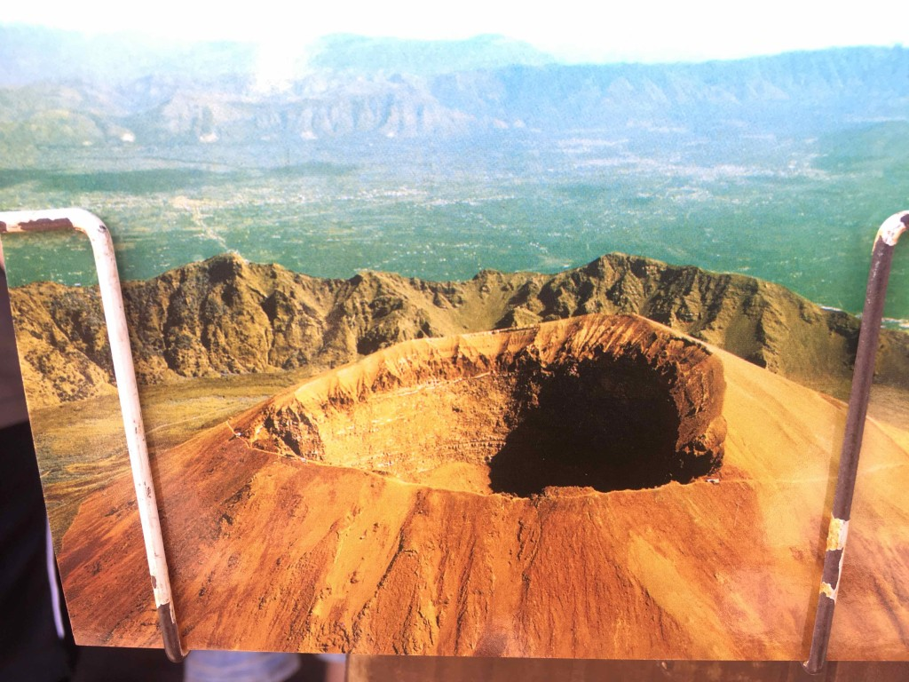A photo of a postcard with the drone's view of the crater.