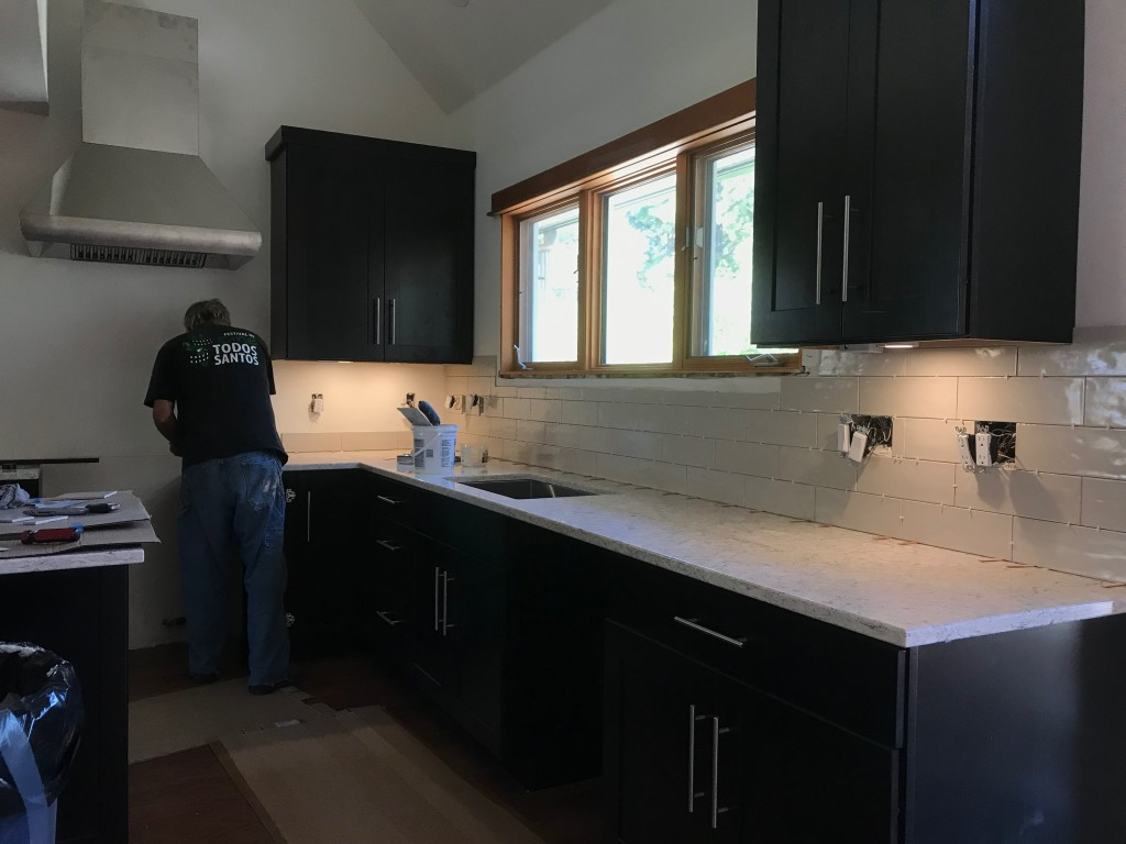 Installing the tile backsplash.