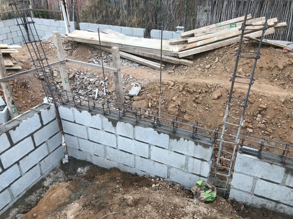 Filling the foundation blocks with concrete.